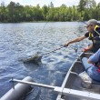 Smartphone photo of boys fishing in a canoe and ca...