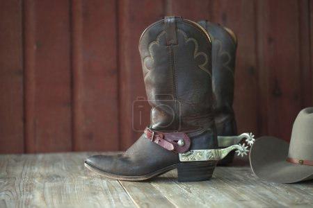 Cowboy boots, spurs and hat on old wood background