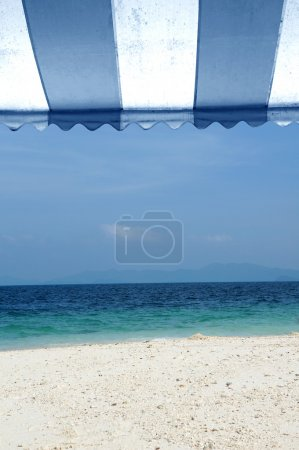 Awning over bright sunny blue sky and beach sea