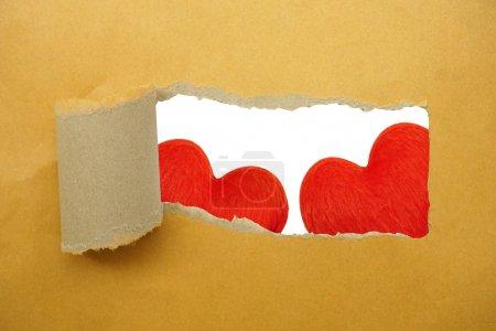 Red heart under torn paper strip