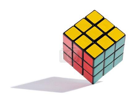 Photo pour Rubiks colorés résolus Cube équilibré sur le bord, un jeu de puzzle nécessitant toutes les carrés d'une couleur particulière être disposé de chaque côté du cube, sur un fond blanc avec une ombre - image libre de droit