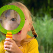 Girl in the garden with a magnifying glass looking...