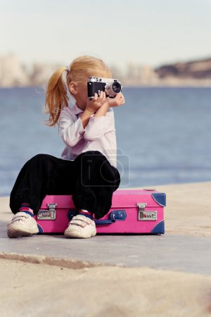 Photo for The girl with the camera sitting on a suitcase on the beach - Royalty Free Image