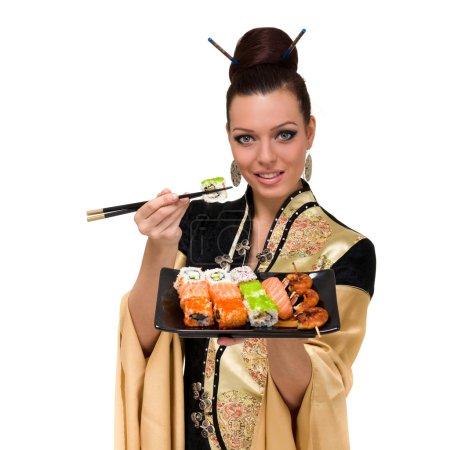 Photo pour Femme portant une robe traditionnelle de manger des sushis, isolé sur fond blanc. - image libre de droit