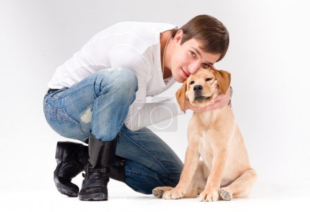 Handsome man with dog over gray