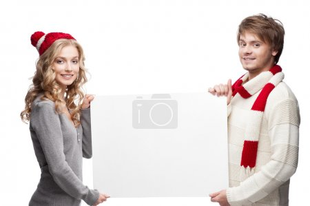 Young happy christmas couple holding big sign