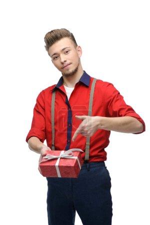 Photo pour Joyeux jeune homme caucasien en tenue vintage rouge et pointant vers cadeau isolé sur blanc - image libre de droit