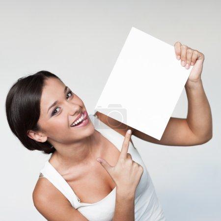 Photo pour Gaie jeune femme en blanc singlett holding et pointant sur signe sur fond gris - image libre de droit
