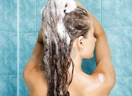 Young attractive woman washing her beautiful long hair