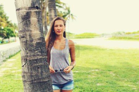 Photo for Cheerful girl wearing trendy shorts and t-shirt walking at summer park. - Royalty Free Image
