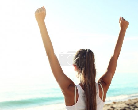 Successful sportswoman raising arms