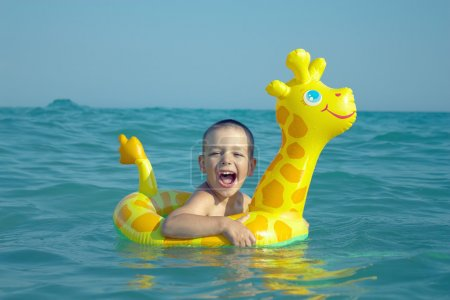 Happy laughing boy enjoying swimming in sea with rubber ring giraffe