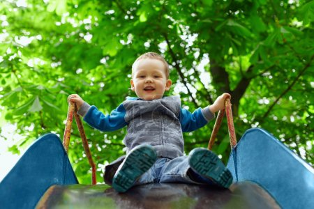 Photo pour Petit garçon s'amuser sur la glissière des enfants dans le parc de printemps - image libre de droit