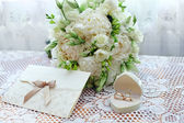 Wedding bouquet, rings and card on lace tablecloth
