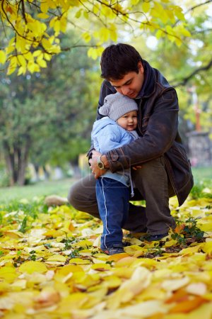 Happy father hugging little son in autumn park among fallen leaves