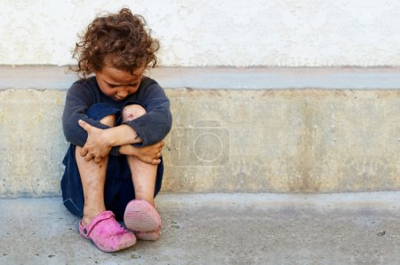 Photo for Poor, sad little child girl sitting against the concrete wall - Royalty Free Image