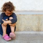 Poor, sad little child girl sitting against the co...