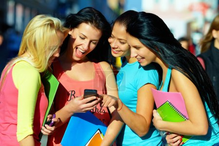 Foto de Grupo de estudiantes mujeres charlando en la red social en el teléfono móvil - Imagen libre de derechos