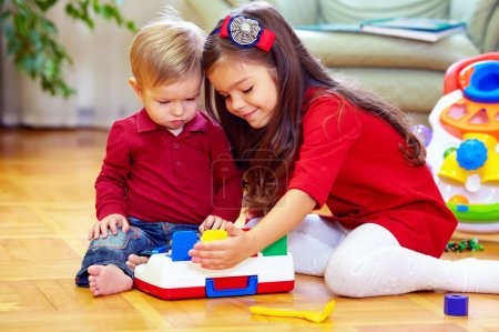 Photo for Beautiful girl playing with little brother at home - Royalty Free Image