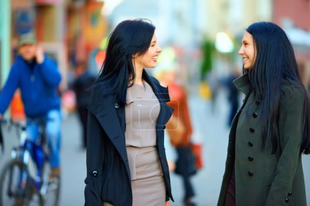 Two happy women talking on crowded city street