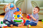 Cute funny baby boys playing with toys at home