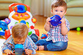 Two little baby boys drinking from feeding bottle, home interior