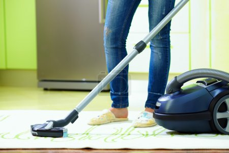 Woman cleaning home with vacuum cleaner...