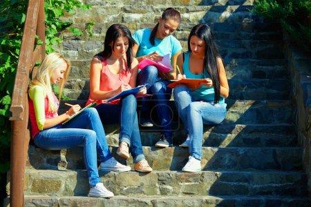 Photo pour Quatre jeunes étudiants étudient en plein air - image libre de droit
