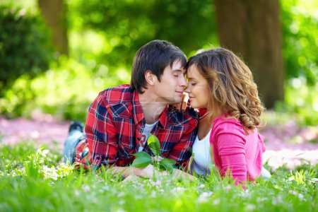 Beautiful couple in love lying on green grass