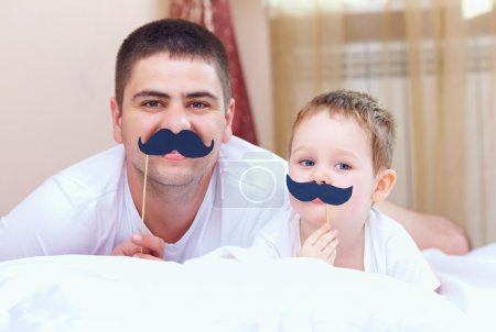 funny father and son with false mustaches, playing at home