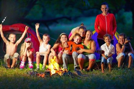Photo pour Des enfants heureux s'amuser autour du camp de feu - image libre de droit