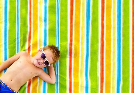 Photo pour Enfant heureux bronzer sur couverture colorée - image libre de droit