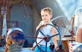 Cute child boy pretends driving an imaginary car