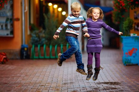 Photo for Happy kids jumping under the rain - Royalty Free Image