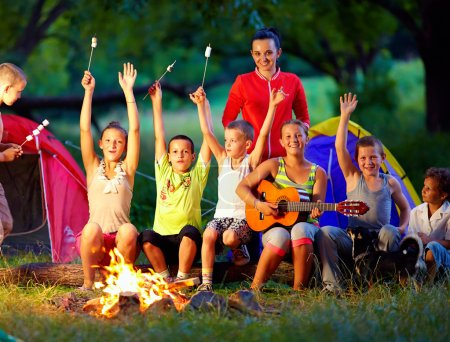 Happy kids singing songs around camp fire