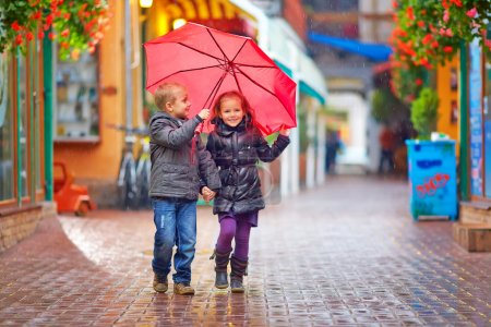 Photo for Happy kids walking under the rain on colorful street - Royalty Free Image