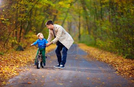 Photo pour Père enseigne à son fils à faire du vélo - image libre de droit