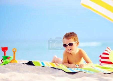 Cute boy kid sunbathing on the beach
