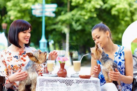 beautiful girls with pets sitting in street cafe