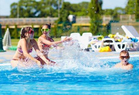 happy teenage kids splashing the water in pool