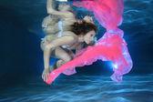"""Постер, картина, фотообои """"Молодая женщина под водой с розовым фуляр"""""""