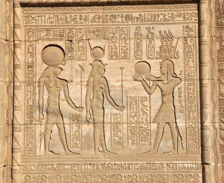 Photo pour La déesse hathor soutenu par horus étant présenté avec le disque solaire par osiris portant la Couronne atef triple à l'ancien temple égyptien de la fertilité et l'amour de t - image libre de droit
