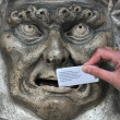 A woman pushes a discreet note into the lion's mou...
