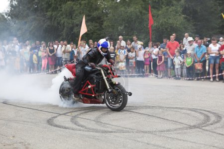 Smoke from the wheel of the motorcycle Alexei Kalinin motorcycle show in the village Verhovazhe, Vologda region, Russia