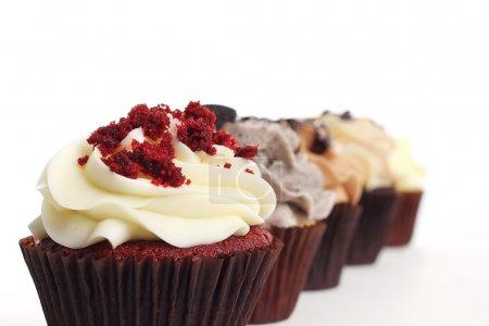 Photo pour Cupcake de velours rouge dans une rangée de petits gâteaux - image libre de droit