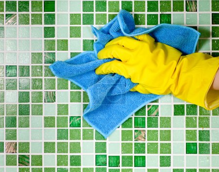 Photo for Hand in yellow protective glove cleaning mosaic wall - Royalty Free Image