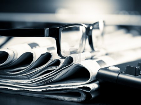 Photo for Glasses on stack of newspapers, very shallow focus - Royalty Free Image