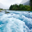 Milky blue glacial water of Briksdal River in Norw...
