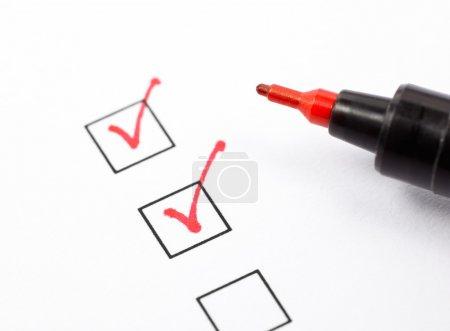 Photo pour Plan rapproché des cases à cocher remplies avec stylo rouge - image libre de droit