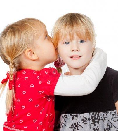 Portrait of little girl telling a secret to her fr...